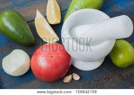 Ingredients for latinamerican mexican sauce guacamole (avocado, tomatoes, lemon, onion, garlic, lime) on wooden background