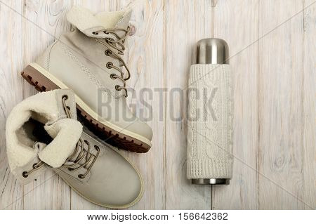 Winter light boots and a thermos in the knitted cover on the bright wooden background.