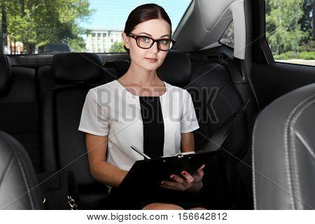 Beautiful woman with clipboard in car