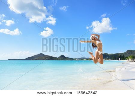 Happy Santa hat girl jumping of joy and fun on Christmas holiday travel in Caribbean beach destination. Winter vacation getaway woman.