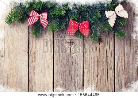 Christmas wooden background with fir tree and ribbon bow decor. View with copy space for your text. Toned