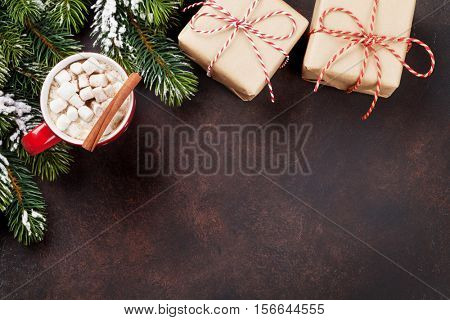 Christmas background with gift boxes, fir tree, hot chocolate and marshmallow. Top view with copy space