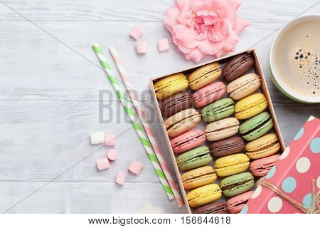 Colorful macaroons and coffee on wooden table. Sweet macarons in gift box. Top view with copy space for your text
