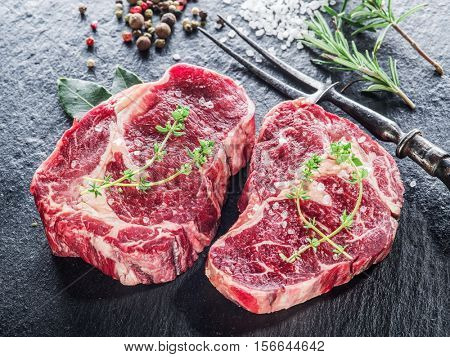 Rib eye steak with spices on the black background.