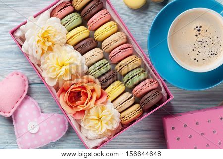 Colorful macaroons and coffee on wooden table. Sweet macarons in gift box and hearts. Top view