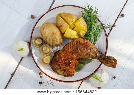 Leg Of Chicken Served With Potatoes In Jackets