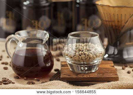 Pot of freshly brewed coffee with glass of  green coffee bean