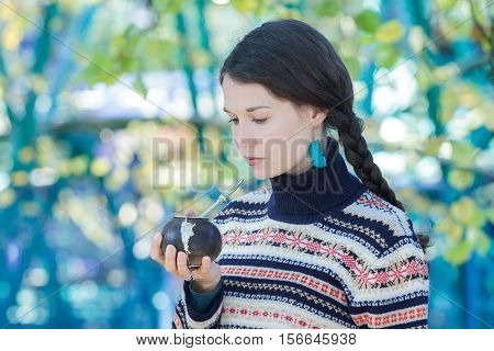 Woman wearing knitted snowflakes pattern sweater and turquoise earrings is drinking hot yerba mate