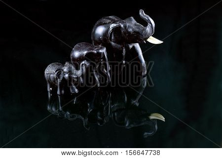 Three small elephant statues with black background.
