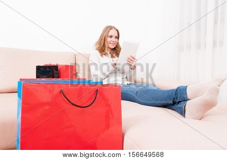 Smiling Lady Shopper Holding Tablet Laying On Couch