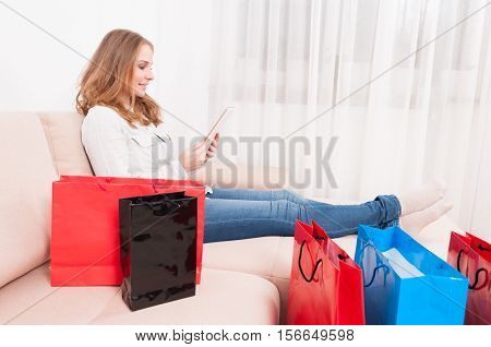 Smiling Woman Shopper Holding Tablet Laying On Couch