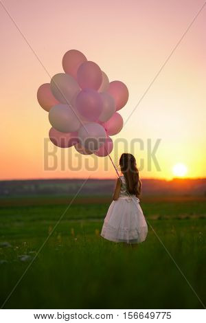 Little girl with balloons at sunset
