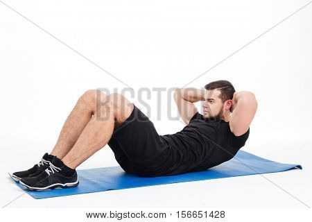 Fitness man shakes press in studion. on mat. isolated white background
