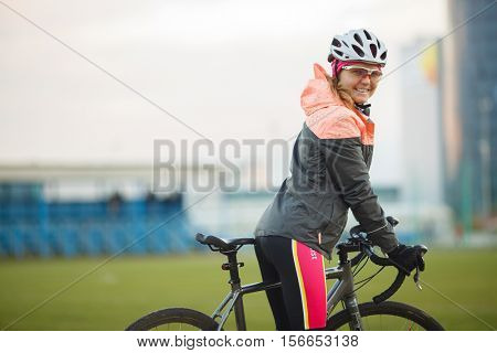 Portrait of smiling female bicyclist in tracksuit outdoors