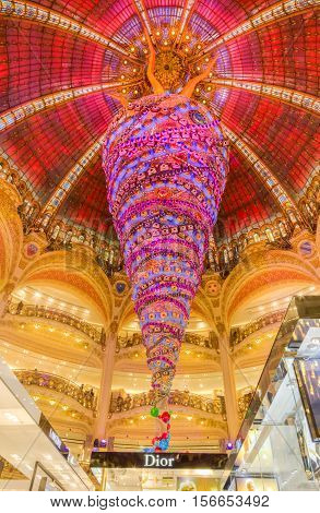 ParisFrance- December 21 2014: Upper part of the Dior stand and the beautiful decorated Christmas decoration in Galleries Lafayette in Paris.