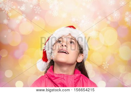 Cute girl in santa hat pretending to be amazed by digitally generated colorful background