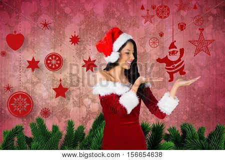 Woman in santa costume pretending to hold imaginary santa claus against digitally generated christmas background