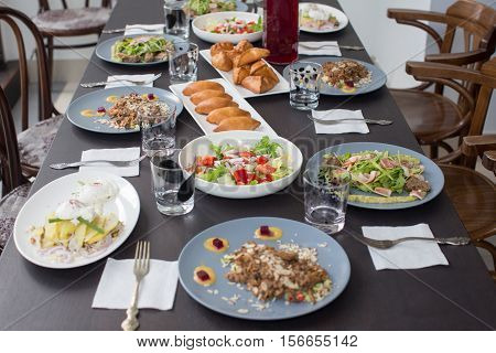 Table laid for a family dinner: pies, salads, fruit drink, forks, glasses plates