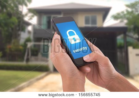 Hand holding mobile phone with concept technology home security system.