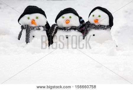Three cute snowmen in a row sat in the snow wearing hats and scarfs. Copy space for text below