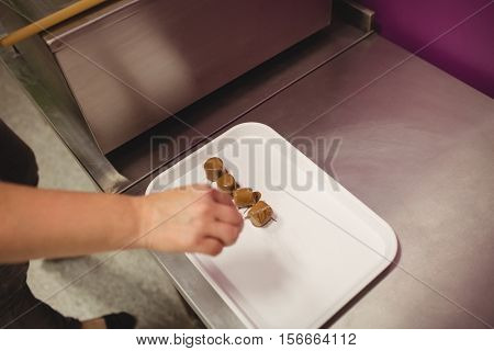 Worker arranging chocolate coated marshmallows on tray in kitchen