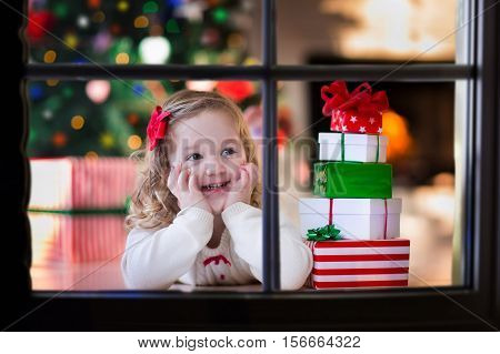 Family on Christmas morning at fireplace. Kids opening Xmas presents. Children under Christmas tree with gift boxes. Decorated living room with traditional fire place. Cozy warm winter day at home.