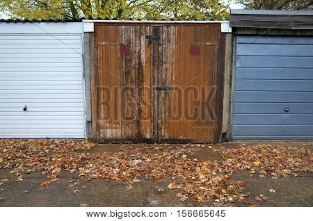 Dilapidated wooden garage doors with peeling paint in a row of garages for motor cars