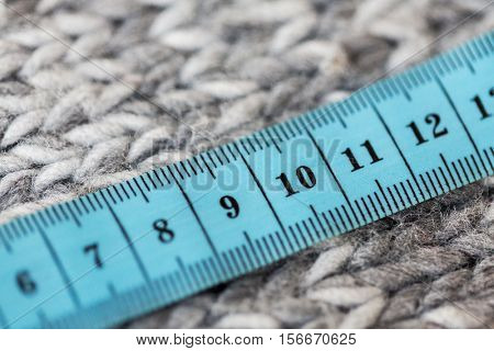 handicraft, knitwear and needlework concept - close up of knitted item with measuring tape