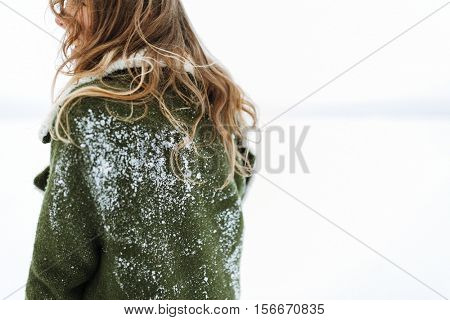 a woman`s hair and back covered with snow