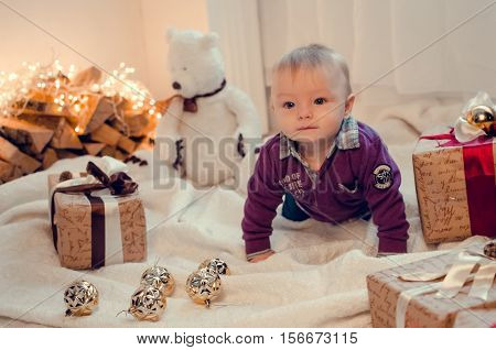 Little cute baby boy in Christmas time with gifts and presents. Holidays time. Merry Christmas and Happy New Year. Baby first Christmas. Beautiful little baby celebrates Christmas.