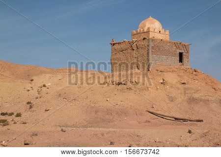 Old and not finished construction of a mosque on hill beside the road to the city Ait Ben Haddou. Dome without a tower. Bright blue sky. Orange sandy soil.