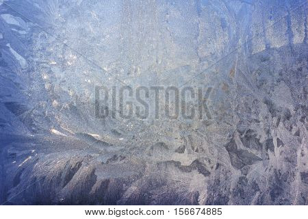 Frosty Patterns on the Blue Frozen Window with Bright Light and Stars, Abstract Winter Frozen Blue Background of Ice
