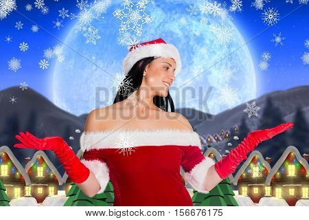 Smiling woman in santa costume pretending to catch snowflakes against digitally generated background