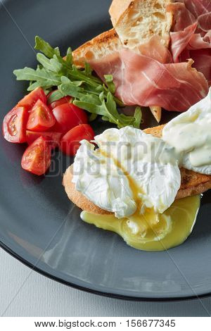 Eggs Benedict with bacon, toast and salad.