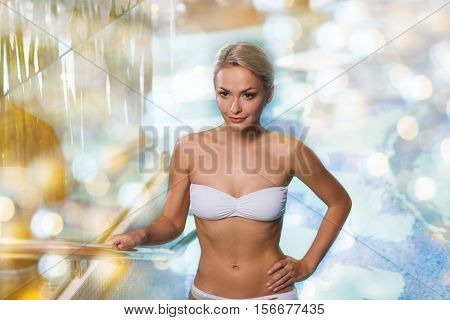 people, beauty, spa, healthy lifestyle and relaxation concept - beautiful young woman in bikini swimsuit raising upstairs in swimming pool over holidays lights background