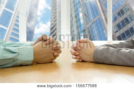 Negotiation of two businessman with clasped hands in office.