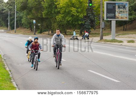 DNEPR UKRAINE - SEPTEMBER 25 2016:Active young father with son and daughter having bicycle ride on a Dnepr river embankment at weekend in Dnepr city, Ukraine at September 25,2016