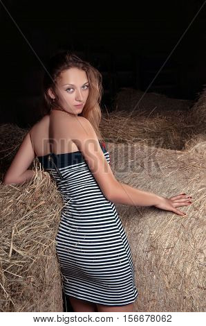 Beautiful young girl with blond hair is in the hayloft