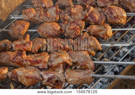Pieces of pork meat cooked outdoor on smouldering carbons