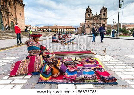 Peru Nov. 9 2015: Unidentified native weavers, dressed in traditional clothing, demonstrate their handicraft. Cusco.