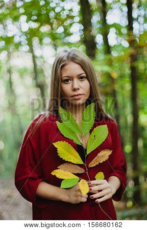 Blonde girl in a misterious forest holding a branch of a tree with autumn colors