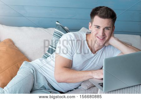 Good mood. Delighted handsome young man smiling and using laptop while lying on the sofa.