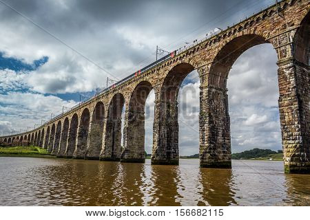 View Of The Train Passing Through The Old Stone Bridge In Scotland