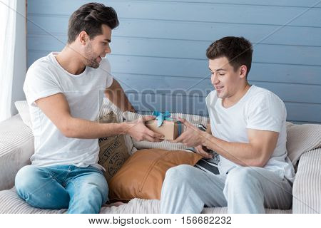 Non-traditional relationship. Handsome relaxed joyful man smiling and accepting a gift from his male friend while sitting together on a sofa at home.
