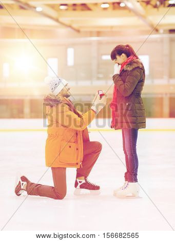 people, love, proposal, sport and leisure concept - happy couple with engagement ring on skating rink