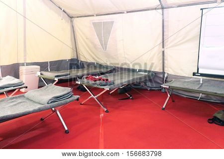 Shelter camp interior with beds and blankets ready for refuges