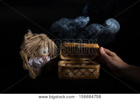 Still life with a casket and rag doll. Black background and the smoke.