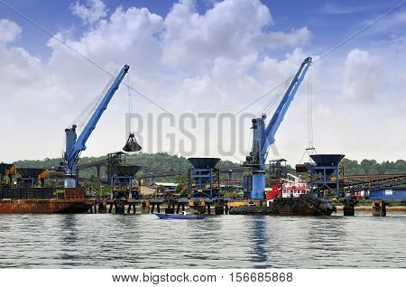 two crane unloading coal from barge to hopper at the coal port