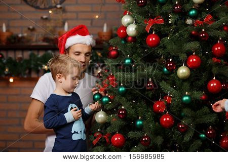 Dad with his son near Christmas tree