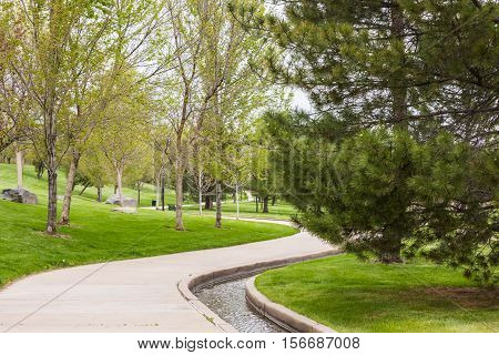 Urban park with concrete walk and gultch in late Spring.